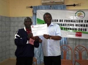 Ilboudo Amadou de ASEPT reçoit son attestation des mains du coordonnateur du RODEB
